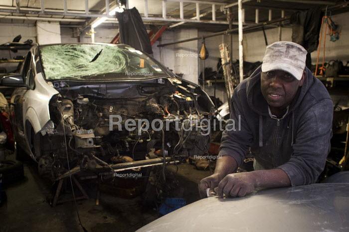 A mechanic repairs a car in a lockup, Railway Arches Peckham. - Connor Matheson - 2014-05-24