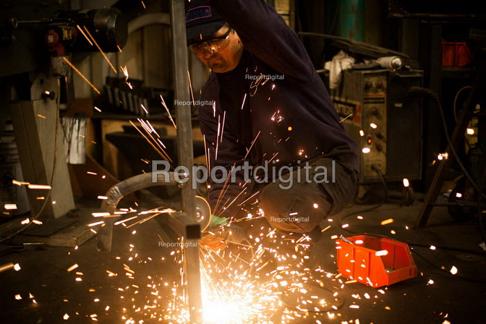A Romanian steel fabricator cuts a steel staircase without goggles, Railway Arches Peckham. - Connor Matheson - 2014-05-26