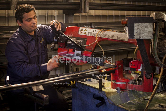 A Bulgarian steel fabricator cuts peices of metal for fabrication, Railway Arches Peckham. - Connor Matheson - 2014-05-26
