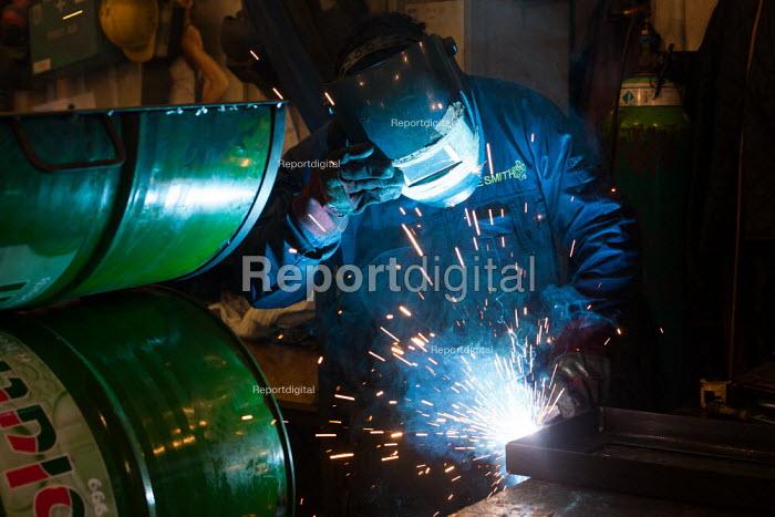 A Bulgarian steel fabricator welds a traditonal jamaican oil drum BBQ, Peckham railway arches. - Connor Matheson - 2014-05-26