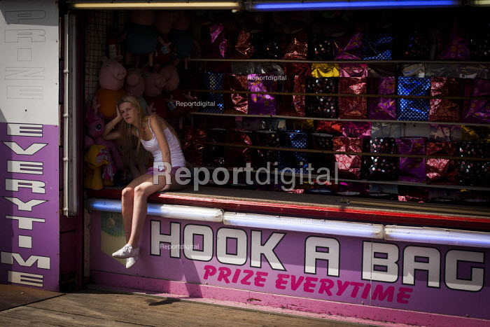 A young girl resting in the shade while at work. Hook a bag stall, Central pier, Blackpool - Connor Matheson - 2014-07-21