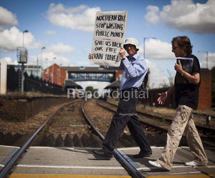 "Paul Nuttall, who is a member of B.R.A.G and a ""Freedom Rider"" that was recently arrested at Sheffield train station for fare evasion, marches around Barnsley train station to demonstrate against cuts to free rail travel for pensioners. Barnsley, South Yorkshire. - Connor Matheson - 2014-07-28"