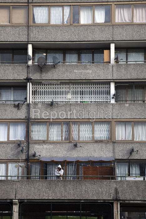 A man smokes on his balcony at the Aylesbury estate, London. - Connor Matheson - 2012-02-06