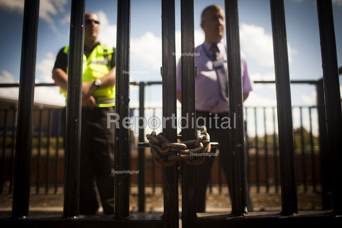 Northern rail staff stand by a chained gate to Barnsley train station in order to stop disabled freedom riders with valid train passes from gaining access to the platform. The gate is usualy open and is the easiest way for a disabled person to gain access to the station. Barnsley, South Yorkshire. - Connor Matheson - 2014-07-28