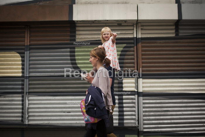 A young family walking past a mural on an abandoned shop front. Rotherham cenre, South Yorkshire. - Connor Matheson - 2014-07-30