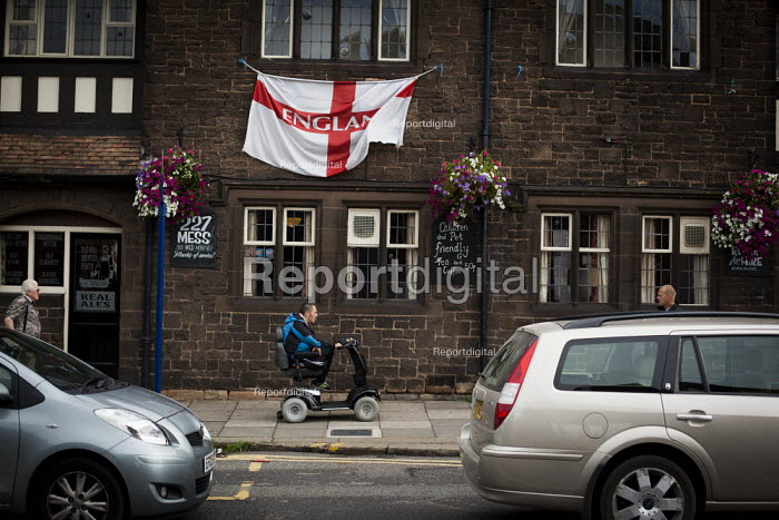 A man on a mobility scooter rides past an england flag outsiide a pub. Rotherham Centre, South Yorkshire. - Connor Matheson - 2014-08-28