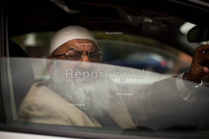A Pakistani man in his car out side Chapel Walk Mosque. Rotherham Centre, South Yorkshire. - Connor Matheson - 2014-08-29