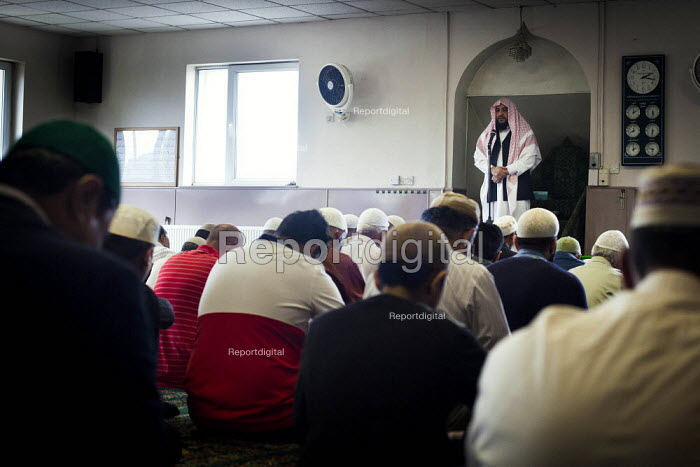 An Imam leads his congregation inside Chapel Walk Mosque. Rotherham Centre, South Yorkshire. - Connor Matheson - 2014-08-29