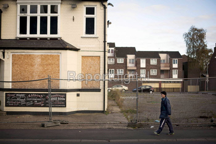 A view of housing. Woman walking past a closed pub. Scunthorpe, North Lincolnshire. - Connor Matheson - 2014-10-29
