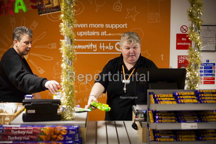 A staff member pricing products. The Community Shop, Goldthorpe, South Yorkshire. - Connor Matheson - 2014-12-16