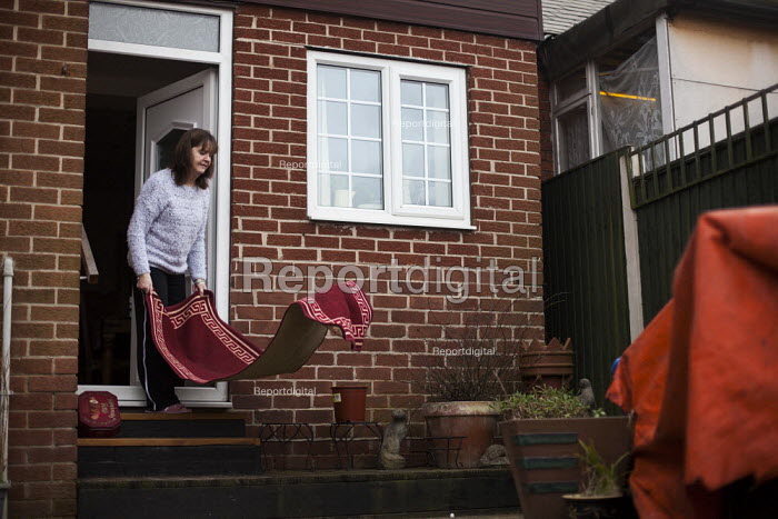 A women cleaning her rug in her back garden. Ryhill, Wakefield, South Yorkshire. - Connor Matheson - 2015-02-28