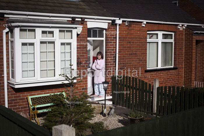 The wife of an ex miner looking out onto her street of an ex pit village. Ryhill, Wakefield, South Yorkshire. - Connor Matheson - 2015-03-01