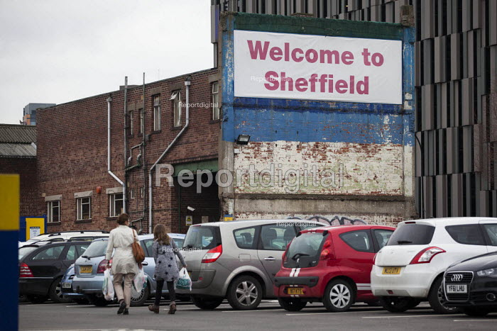 A woman and her daughter walking through a car park with a welcome to Sheffield sign. Sheffield, South Yorkshire. - Connor Matheson - 2015-03-14