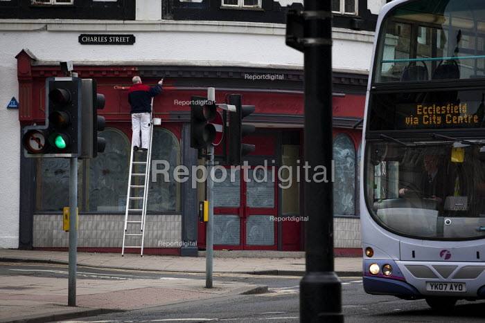 A man painting the outside of an empty shop while a bus is driving past. Sheffield, South Yorkshire. - Connor Matheson - 2015-03-15