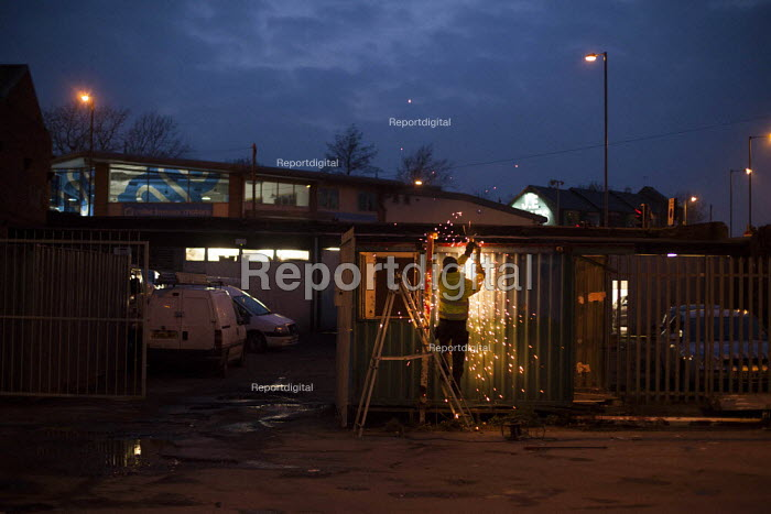 A worker grinding a metal fence at night. Highfield, Sheffield, South Yorkshire. - Connor Matheson - 2015-03-18