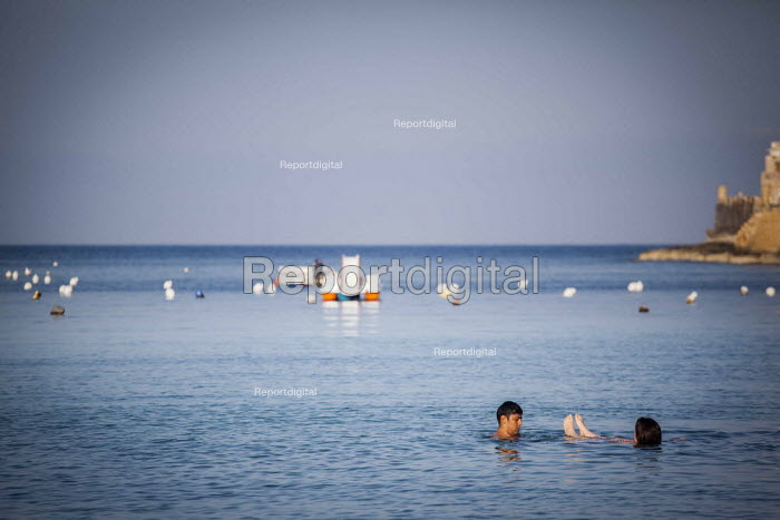 Tourists swimming on a man made city beach. Saint Julians, Tourism is a vital industry for the maltese economy, contributing 15 to its GDP. Since 2009 Malta has experienced a 10 drop in tourism. Malta. - Connor Matheson - 2015-04-21