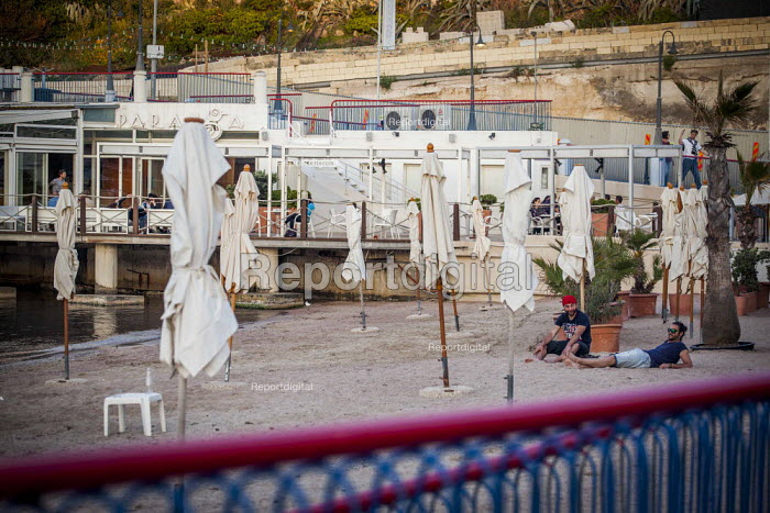 Tourists relaxing on a man made beach. Tourism is a vital industry for the maltese economy, contributing 15 to its GDP. Since 2009 Malta has experienced a 10 drop in tourism. Saint Julians, Malta. - Connor Matheson - 2015-04-21