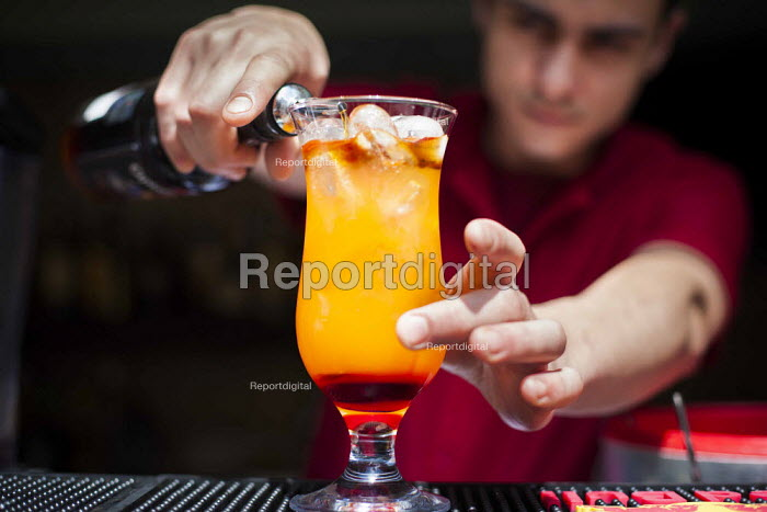 A hotel worker making a tequilla sunrise cocktail. Tourism is a vital industry for the maltese economy, contributing 15 to its GDP. Since 2009 Malta has experienced a 10 drop in tourism. Tropicana Hotel. Saint Julians, Malta. - Connor Matheson - 2015-04-21