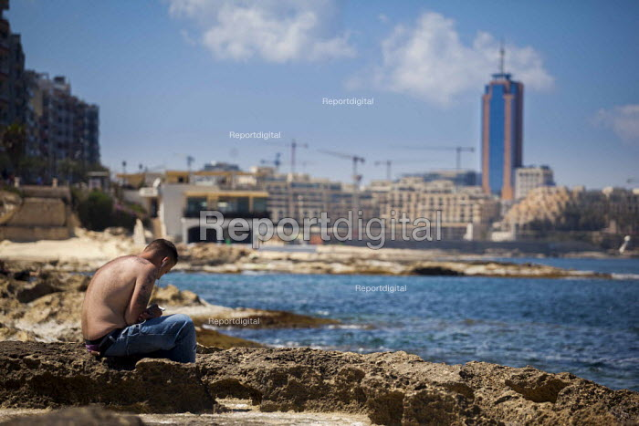 A local workman relaxes by the sea while listening to his Ipod with the Hilton Hotel and Sain julians in the background. Sliema, Malta. - Connor Matheson - 2015-04-22