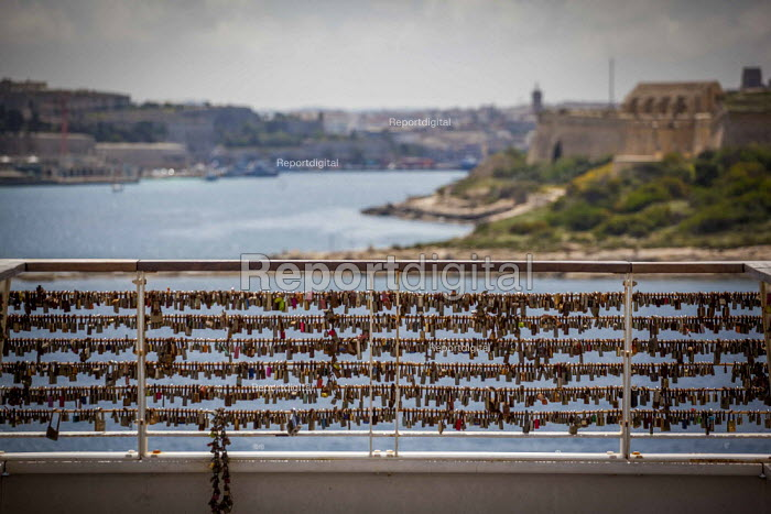 Love locks locked onto a railing at The Point, overlooking the sea and Valletta. Love locking is a trend of locking padlocks to a bridge or railing in order to symboloise love. The trend has been cotreversial, particularly in Paris where the trend is widespread. sliema, Malta. - Connor Matheson - 2015-04-23