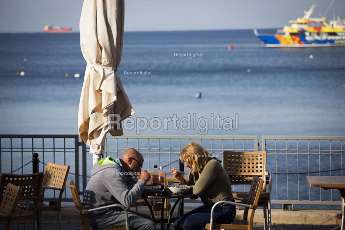 Tourists having dinner by the sea. Tourism is a vital industry for the maltese economy, contributing 15 to its GDP. Since 2009 Malta has experienced a 10 drop in tourism. Bu�ibba, Malta. - Connor Matheson - 2015-04-23