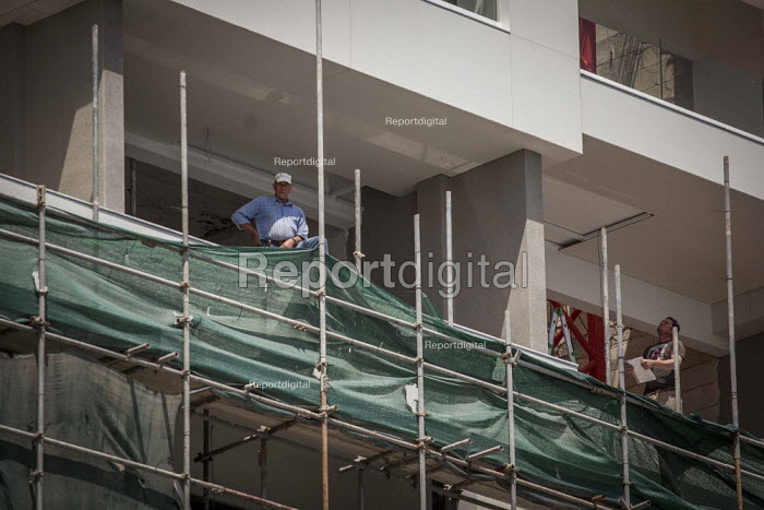 Construction workers without helmets and saftey gear, building a hotel. Sliema, Malta. - Connor Matheson - 2015-04-23