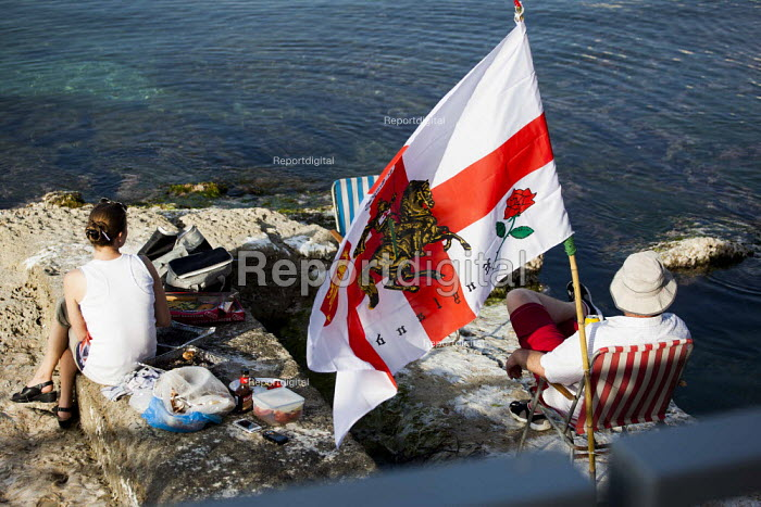 English tourists abroad, having a beer and a BBQ by the sea with a flag. Tourism is a vital industry for the maltese economy, contributing 15 to its GDP. Since 2009 Malta has experienced a 10 drop in tourism. Bugibba, Malta. - Connor Matheson - 2015-04-23