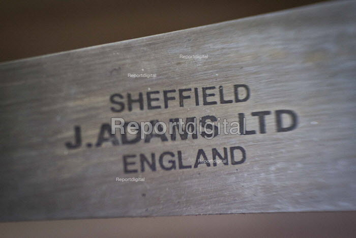 J Adams logo on a finished knife. J Adams and Sons manufacture a range of military and cooking knives out of steel using traditional hand based production methods. The family business employs around 16 people part time and has been passed down from son to son for three generations. Much of the knives are exported for the American market. J, Adams and Sons Cutlers and Knives factory, Sheffield centre, South Yorkshire. - Connor Matheson - 2015-05-18
