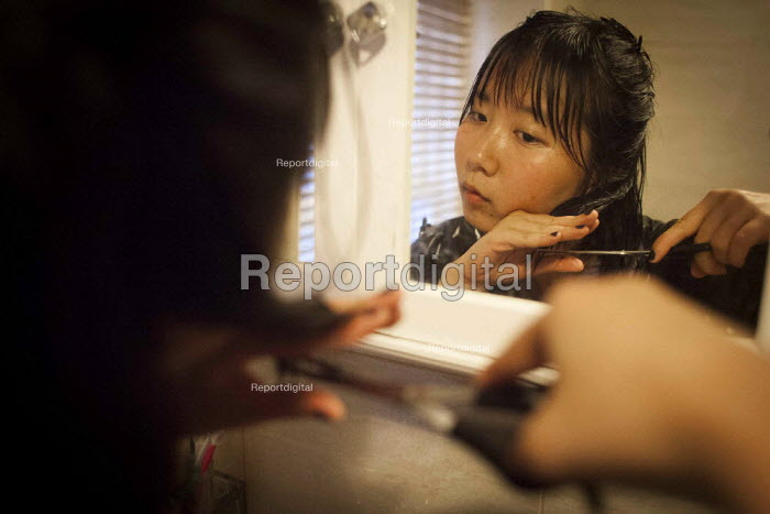 A Chinese student cutting her own hair in order to sell it to Bloomsbury Wigs in London. She hopes to get around �50 for her hair which was 19 inches long. Some people with rare hair types have made a lot of money from selling their hair. Sheffield, South Yorkshire. - Connor Matheson - 2015-06-16