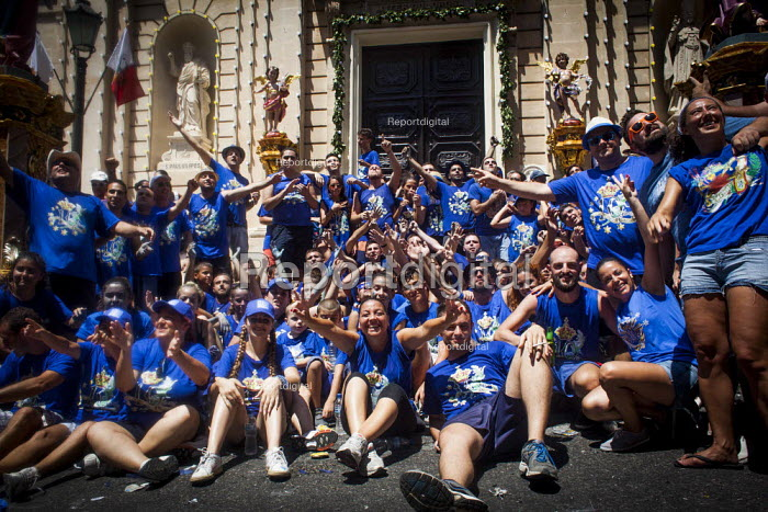 Local volunteers who organised and took part in the celebration pose, The Feast of Our Lady of Sorrows St. Pauls Bay Malta, cheering and jumping in the air outside the village church - Connor Matheson - 2015-07-26