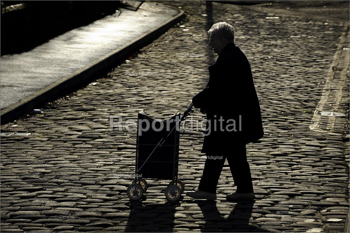 Pensioner with his shopping trolley crossing a cobbled street. - Christopher Thomond - 2008-11-18