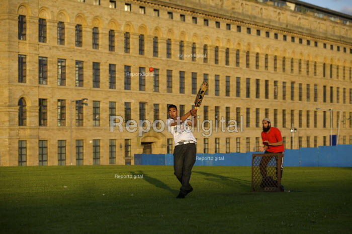 Young men play an impromptu cricket match outside Lister's Mill in Bradford, once the largest silk factory in the world, now partly renovated turned into an apartment block. - Christopher Thomond - 2009-07-27