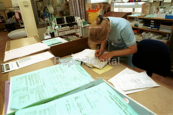 Nurse catching up on paperwork on a ward at a North London Hospital - Duncan Phillips - 2000-09-16