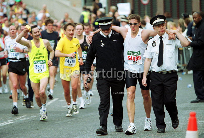 Injured runner being helped by St John Ambulance Brigade Volunteers Flora London Marathon - Duncan Phillips - 2002-04-14