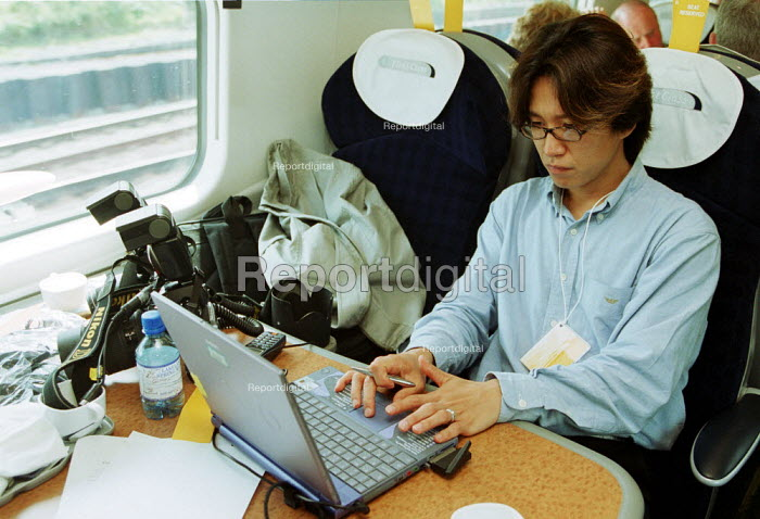Photographer using a laptop and digital camera to transmit photographs on a train. - Duncan Phillips - 2002-07-23