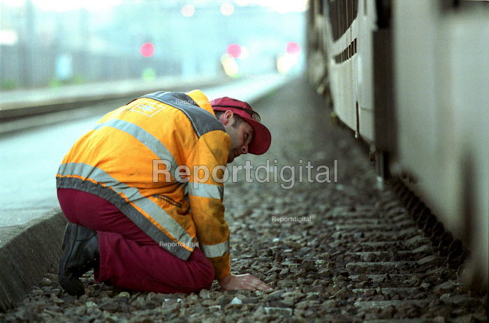 Railway worker checking for hidden Immigrants aboard Freight containers at EWS freight Depot outside the Channel Tunnel Kent. - Duncan Phillips - 2001-05-27