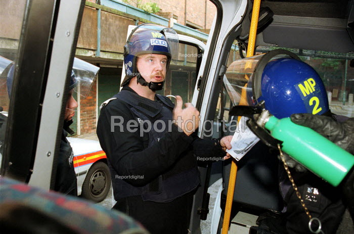 Police Officer in Riot Gear briefing other officers regarding entering a property where it is suspected that Hard Drugs are being sold - Duncan Phillips - 2002-05-27