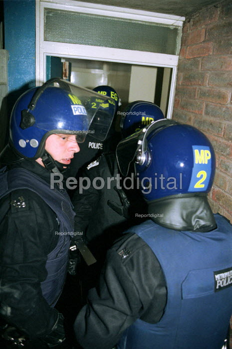 Police Officer in Riot Gear entering a property where hard drugs are suspected of being sold. - Duncan Phillips - 2002-05-27