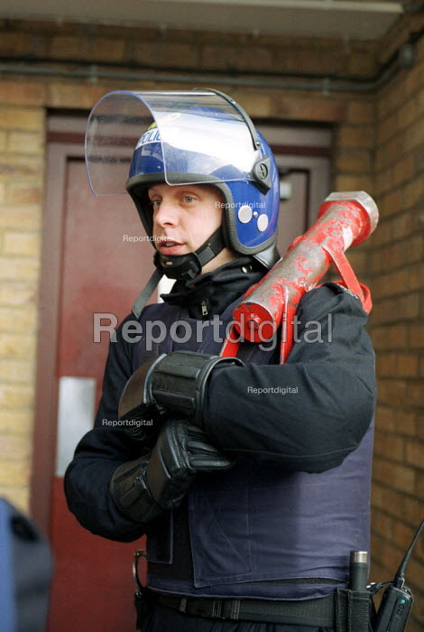 Police Officer in Riot Gear Holding - the Enforcer - a device used as a battering ram to gain forced entry to a property during a drugs raid. - Duncan Phillips - 2002-05-27