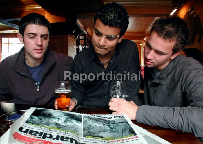 Sheffield University students reading newspaper story about the first photographs depicting American bombing of Afghanistan - David Bocking - 2001-10-10