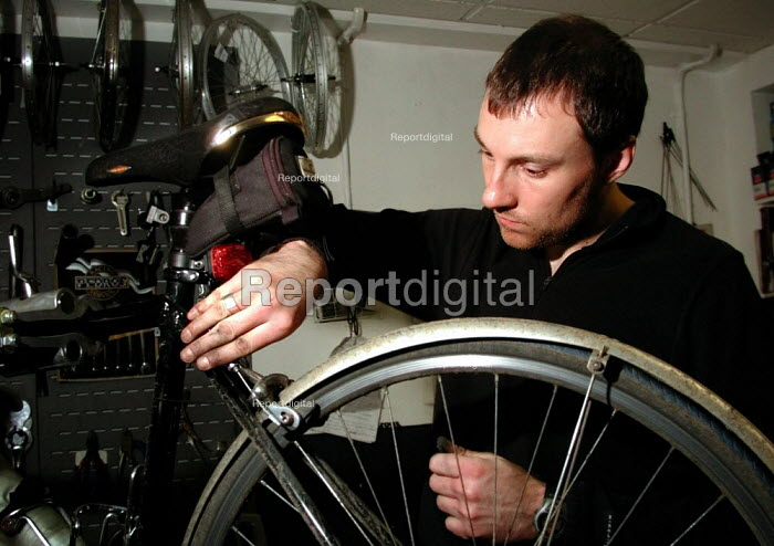 Cycle shop mechanic checking a repaired wheel - David Bocking - 2001-12-07