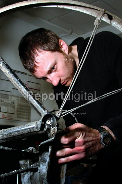 Cycle shop mechanic checking a repaired wheel - David Bocking - 2001-12-07