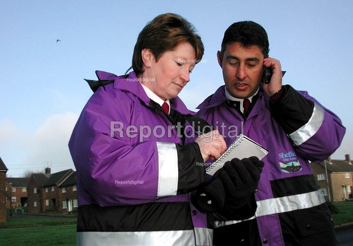 Neighbourhood wardens checking notes before calling into the housing office by mobile phone while working on the Lowedges council estate in Sheffield - David Bocking - 2001-12-10