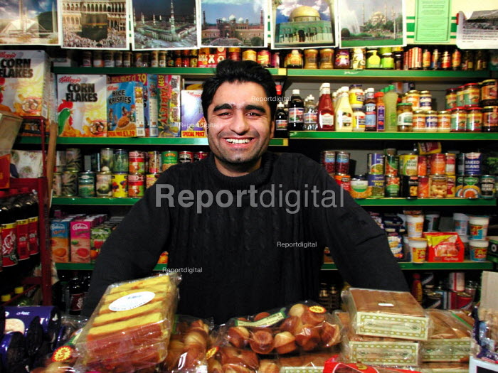 32 year old Corner Shop owner in front of some of his stock (and pictures of famous Mosques), Sheffield - David Bocking - 2002-01-08
