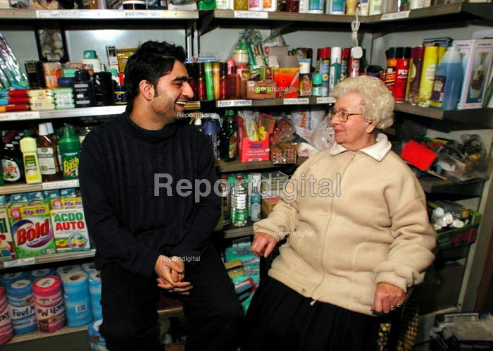 32 year old corner shop owner talking to a customer at the back of his store in Sheffield - David Bocking - 2002-01-08