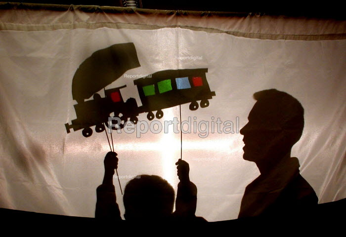 Fathers and kids day at a Sheffield library a father admiring a shadow puppet made by his son for a play specially written by the children, their fathers and library staff. The days activities were aimed to encourage fathers to help their children with reading. - David Bocking - 2004-06-19