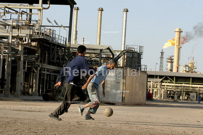 Workers playing soccer in the Basra oil refinery. Workers in Iraqs oil industry have organized one of the strongest unions in Iraq, and are trying to prevent the privatization of the oil industry by the US and British occupying forces. - David Bacon - 2005-05-28