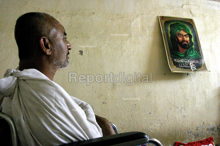 A worker disabled in an oil refinery accident at home in Basra, with a picture of the Muslim martyr Hussein on the wall - David Bacon - 2005-05-25