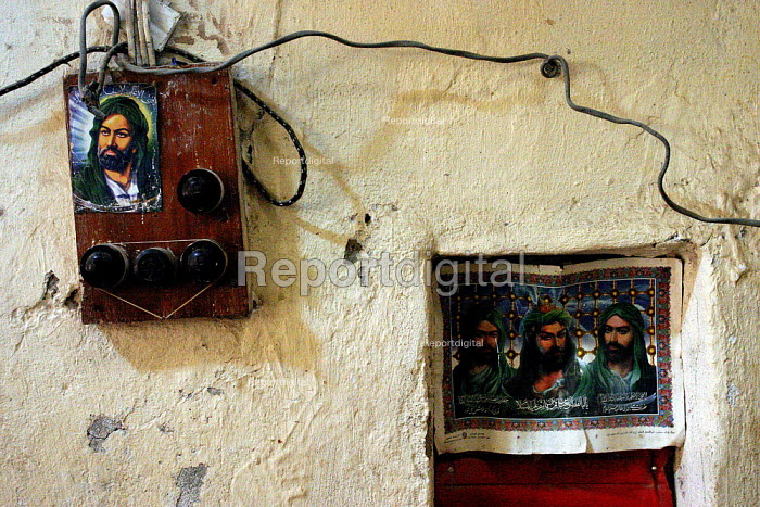 Small pictures of Muslim martyrs decorate electrical panels in a Basra oil workers home. - David Bacon - 2005-05-25