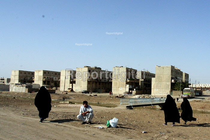 Women walk past apartment buildings built by the government for working class residents of Basra. - David Bacon - 2005-05-26